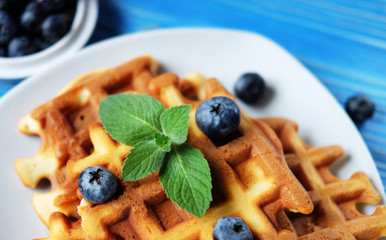 Homemade waffles with blueberries in plate on wooden table
