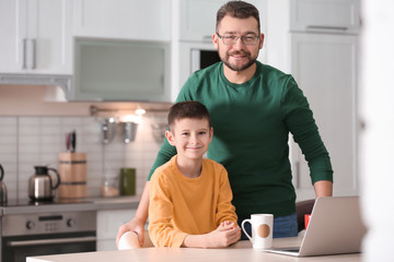 Little boy and his dad using laptop in kitchen