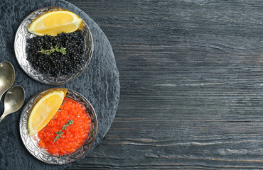 Plates with black and red caviar on wooden background
