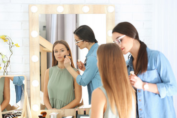 Professional visage artist applying makeup on woman's face in salon