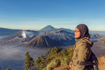 A teenager pose with Bromo mountain as background at East Java Indonesia