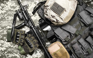 Upper view photo of a military tactacal bulletproof vest, gloves, helmet with american flag badge and rifle laying on camouflage cloth background.