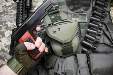 First person view hand in tactical gloves holding a gun on camouflage background with bulletproof vest and cartridge belt.