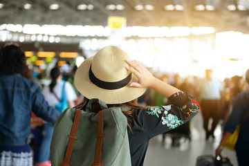 Tourist is confusing by touching her hat while seeing crowded people in the Airport.