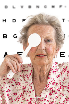 Older lady taking an eyesight test examination at an optician clinic whith Eye Chart Illustrations on background
