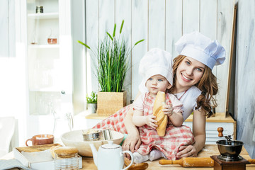 Mother and baby daughter happy and beautiful prepare pastry and flour in the kitchen at home