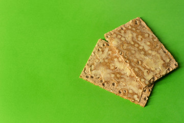 Close-up of rye crackers with butter - on bright green background - minimal- copy space