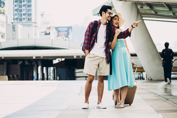 Couple Asian travelers are walking and enjoying vacations on city street. Travel concept
