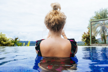 Woman in a pool looking at the jungle seen from behind in Costa Rica