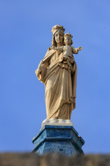 Statue of virgin Mary with child on top