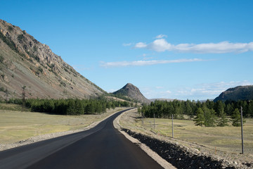 Asphalt winding road in the mountainous area in the summer and sky with clouds