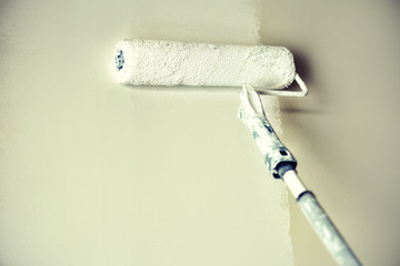 Hand painting wall with paint roller, pastel color. Appartment renovation, repair, building and...