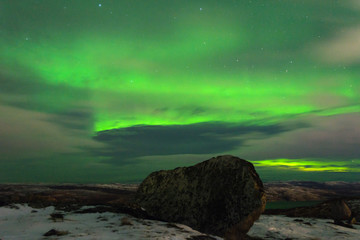 Northern Lights, polar lights over the hills and tundra in winter.Huge stone.