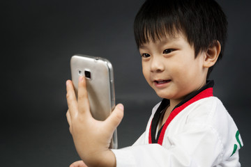 Asian cute boy in karategi costume take a photo by cellphone.