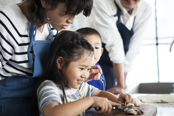 女の子が包丁で具材を切っている。楽しそう。お母さんが教えている。