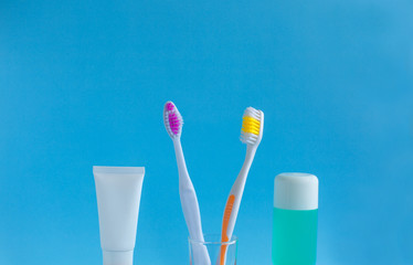 Two toothbrushes in a glass near the toothpaste and rinse against a blue background. The concept of dentistry and health. Free space for copying.
