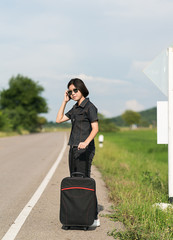 Woman with luggage hitchhiking along a road