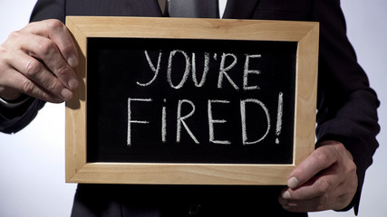 Youre fired with exclamation written on blackboard, businessman holding sign