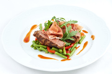 Grilled beef with pork slices and boiled pepper, green beans, fresh arugula and sauce on a white plate.