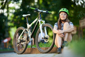 Cyclist in professional cycling clothing and helmet sitting near bike on roadside in green sunny park. Woman performing morning exercise, outdoor acivities. Concept of healthy lifestyle