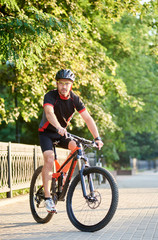 Male biker in cycling sportswear and protective helmet riding on bike near green park. Concept of healthy lifestyle, sport advertising, outdoor activities