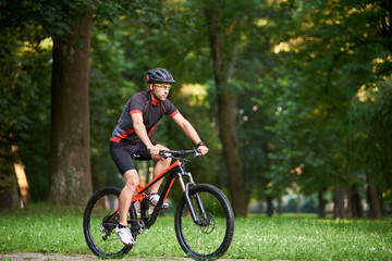 Man biker in cycling clothing and protective helmet training on bicycle, getting ready for race in park on fresh air. Man enjoying morning bike ride. Concept of motivation, healthy lifestyle
