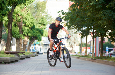 Male cyclist in professional cycling sportswear and protective helmet riding on bike along empty city streets, green trees around. Sportsman performing morning outdoor exercise and training.