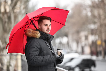 Young man in warm clothes with red umbrella outdoors