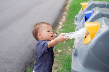 Cute little Asian 18 months / 1 year old toddler baby boy child throwing plastic bottle in recycling trash bin at public park, Eco friendly kid Recycling, Save the world & environment concept