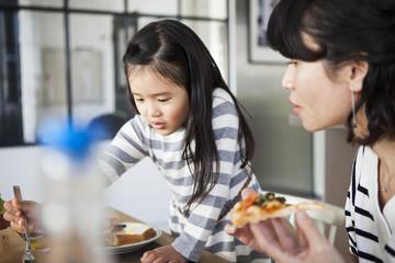 ピザを食べているお母さんと女の子。