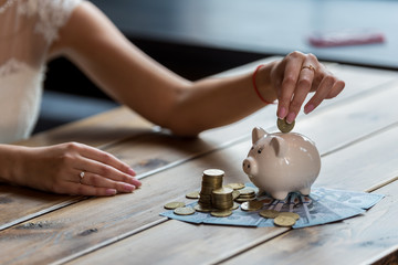 The bride counts the money. Wedding expenses. Bride with a piggy bank