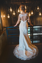 bride in vintage interior alone. Curly blonde hair. Back