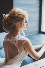 bride in vintage interior alone. Curly blonde hair. Back