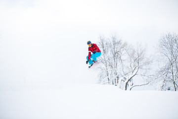 Photo of snowboarder man jumping on snowy hill