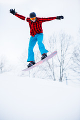 Picture of sports man in helmet with snowboard jumping in snowy resort