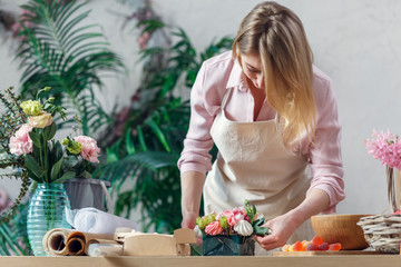 Photo of blonde florist making bouquet of marshmallows, flowers