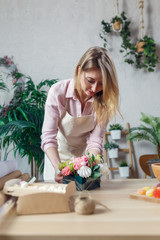 Photo of florist composing bouquet at table on background of flowers