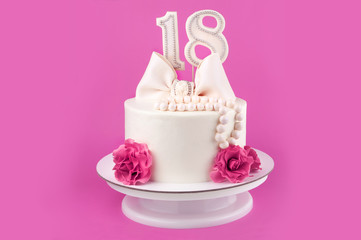 White cake for 18 years decorated with pink flowers, bow and pearl beads from mastic on a pink background.