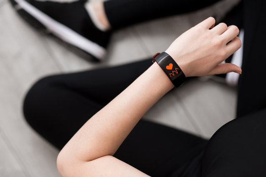 A woman's hand with a smart watch. Heart Rate Measurement. Close-up. Sitting on the floor. Black sportswear. Wooden floor.