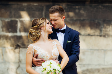 The groom gently embraces his elegant bride who holds the bouquet on the background of the wall