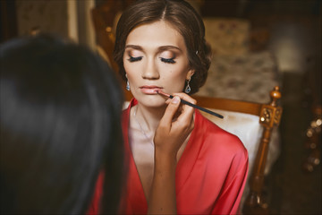 Makeup artist applies makeup for beautiful brunette young woman with sexy lips and closed eyes, wearing in peach peignoir