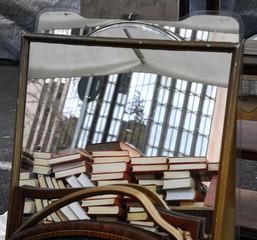 Stand auf einem Flohmarkt in Rom mit Bücherstapeln in einem Spiegel