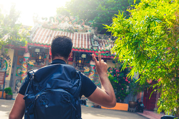 backpacker in front of temple in Thailand doing hand sign , Bangkok , Thailand , Southeast asia