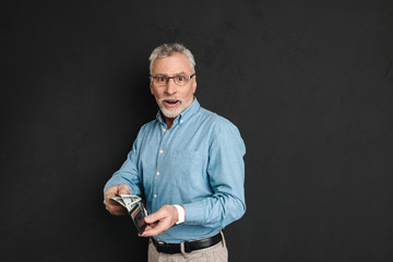 Portrait of adult man 60s with grey hair and beard posing on camera and holding wallet with money, isolated over black background