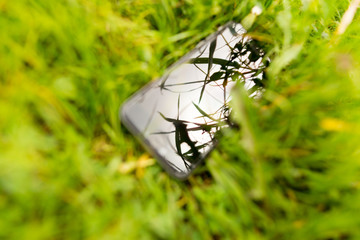 Grass in reflection of a cell phone in nature