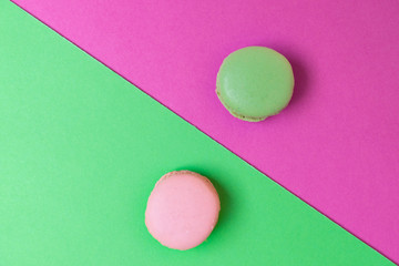 Two colorful macarons on green and pink background