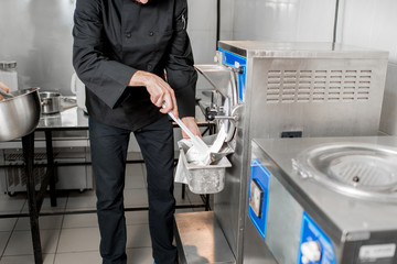 Chef getting white ice cream from the ice cream maker machine in the small manufacturing