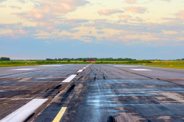Sunrise with landscape airport of wet runway with traces of rubber tires on asphalt.