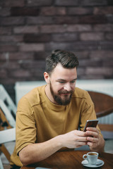 Young man sitting in cafe and using smart phone.