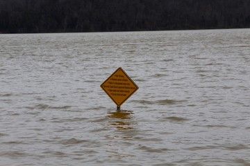 The yellow road sign in the flood waters of the lake.